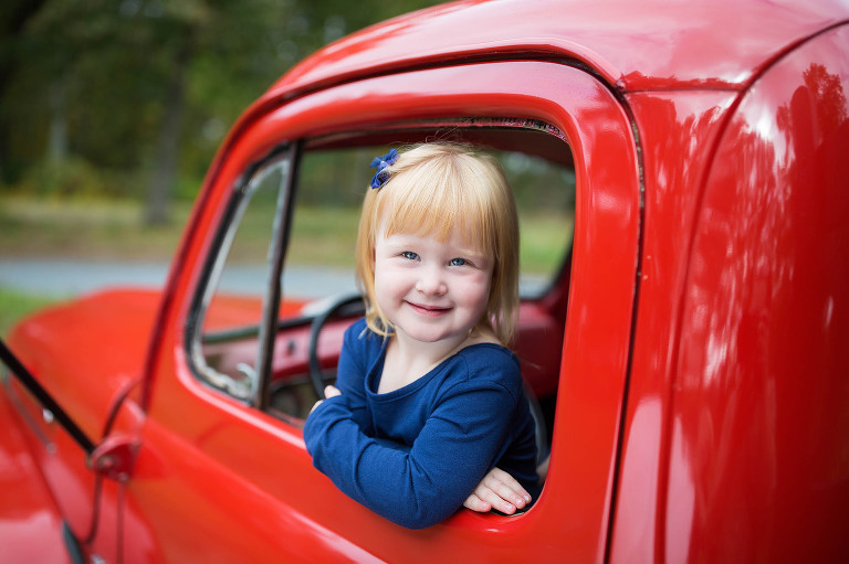 Girl Playing in Red Vintage Truck Smiling